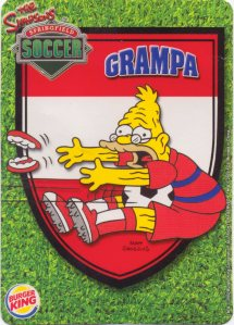 Grampa stops the ball in The Simpsons Springfield soccer team trading cards.
