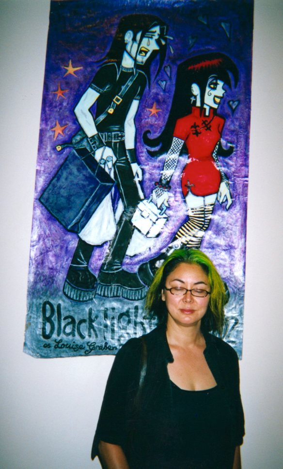 Louise Graber with a painting of a panel from her comic Black Light Angels in the exhibition.